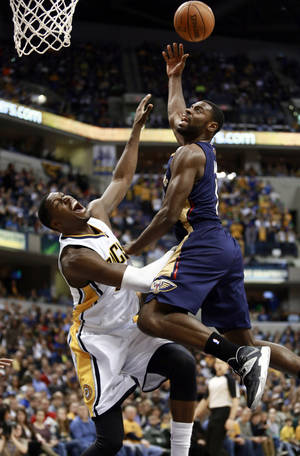 Photo - New Orleans Pelicans guard Tyreke Evans, right, puts up a shot as Indiana Pacers center Ian Mahinmi defends during the second half of an NBA basketball game in Indianapolis, Saturday, Jan. 4, 2014. The Pacers won 99-82. (AP Photo/R Brent Smith)
