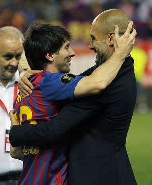 Photo -   FC Barcelona's Lionel Messi from Argentina, left, celebrates his victory with coach Josep Guardiola during the final Copa del Rey soccer match against Athletic Bilbao at the Vicente Calderon stadium in Madrid, Spain, Friday, May 25, 2012. (AP Photo/Andres Kudacki)
