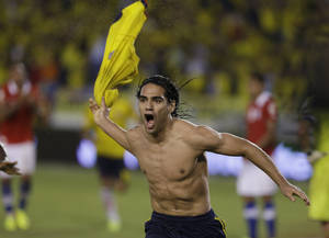 Photo - Colombia's Radamel Falcao Garcia celebrates after scoring from the penalty spot his team's third goal against Chile during a 2014 World Cup qualifying soccer match in Barranquilla, Colombia, Friday, Oct. 11, 2013. (AP Photo/Ricardo Mazalan)