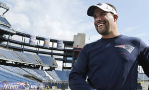 Photo - New England Patriots offensive coordinator Josh McDaniels smiles as he walks off the field at Gillette Stadium before a team NFL football practice in Foxborough, Mass., Monday, July 29, 2013. McDaniels said assistant coaches are progressing slowly in teaching their new, young players. (AP Photo/Charles Krupa)