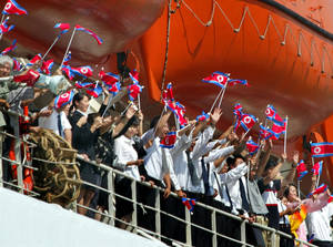 Photo - FILE - In this Sept. 5, 2003 file photo, a group of young Northern-alligned Koreans residing in Japan, among passengers cheer and wave the North Korean national flags from the upper deck on North Korean ferry Mangyongbong-92 upon its departure for the communist country at a port in Niigata, northern Japan. Japan approved easing its sanctions on North Korea on Friday in response to Pyongyang's reopening of a probe into the fate of at least a dozen Japanese allegedly abducted to the North decades ago. (AP Photo/Itsuo Inouye, File)