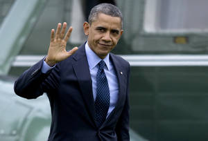 Photo - President Barack Obama waves to the media as he walks from Marine One to the Oval Office of the White House, Thursday, Dec. 20, 2012, in Washington, as he returns from Walter Reed National Military Medial Center in Bethesda, Md., where he visited injured military members. (AP Photo/Carolyn Kaster)