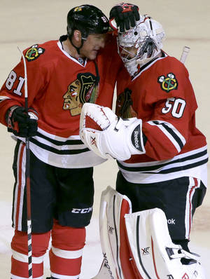 Photo - Chicago Blackhawks goalie Corey Crawford, right, celebrates with Marian Hossa after the Blackhawks defeated the Anaheim Ducks 4-2 in an NHL hockey game in Chicago, Friday, Jan. 17, 2014. (AP Photo/Nam Y. Huh)