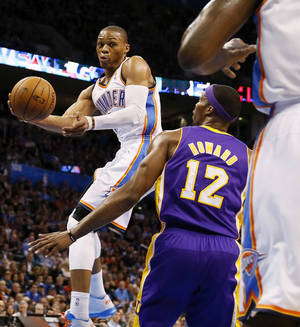 Photo - Oklahoma City's Russell Westbrook (0) passes the ball around Los Angeles' Dwight Howard (12) during an NBA basketball game between the Oklahoma City Thunder and the Los Angeles Lakers at Chesapeake Energy Arena in Oklahoma City, Friday, Dec. 7, 2012. Photo by Nate Billings, The Oklahoman