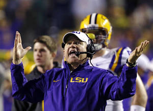 Photo - FILE - In this Nov. 23, 2013, file photo, LSU head coach Les Miles reacts to a touchdown call for Texas A&M that was later overturned on replay during the second half of an NCAA college football game in Baton Rouge, La. Recruiting is the lifeline of college coaches and with teenagers using social media like Twitter to communicate, some football staffs have pushed the boundaries of NCAA regulations to reach top high school recruits. Miles was reminded by LSU administration officials to use caution when taking to Twitter to discuss recruiting. National Signing Day is Wednesday, Feb. 5. (AP Photo/Gerald Herbert, File)