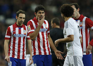 Photo - Atletico's Diego Costa, 2nd left has words with Real's Pepe, 3rd right during a semi final, 1st leg, Copa del Rey soccer derby match between Real Madrid and Atletico Madrid at the Santiago Bernabeu Stadium in Madrid, Wednesday Feb. 5, 2014.  (AP Photo/Paul White)