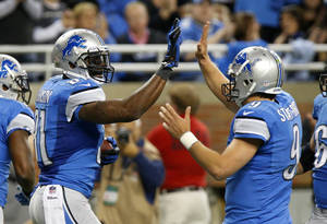 Photo - Detroit Lions wide receiver Calvin Johnson, left, celebrates his 2-yard touchdown reception with quarterback Matthew Stafford (9) during the first half of an NFL football game in Detroit, Sunday, Oct. 27, 2013. (AP Photo/Duane Burleson)