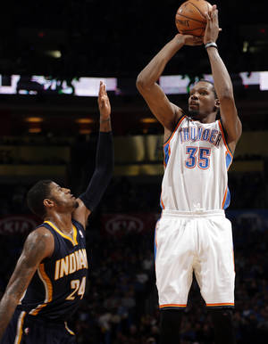 Photo - Oklahoma City's Kevin Durant (35) shoots over Indiana's Paul George (24) during the NBA game between the Oklahoma City Thunder and the Indiana Pacers at the Chesapeake Energy Arena, Sunday, Dec. 8, 2013. Photo by Sarah Phipps, The Oklahoman