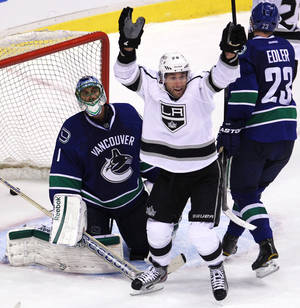 Photo -   Los Angeles Kings center Jarret Stoll (28) celebrates after teammate Willie Mitchell scored against Vancouver Canucks goalie Roberto Luongo (1) during the second period of Game 1 of an NHL hockey first-round playoff series Wednesday, April 11, 2012, in Vancouver, British Columbia. (AP Photo/The Canadian Press, Jonathan Hayward)