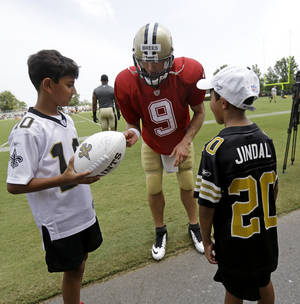 Photo - New Orleans Saints quarterback Drew Brees (9) signs autographs for Shaan Jindal, 11, left, and Slade Jindal, 9, sons of Louisiana Gov. Bobby Jindal, during their NFL football training camp in Metairie, La., Tuesday, July 30, 2013. (AP Photo/Gerald Herbert)
