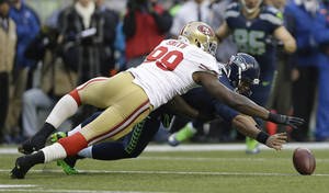 Photo - Seattle Seahawks' Russell Wilson and San Francisco 49ers' Aldon Smith go after Wilson's fumble on the first play of the first half of the NFL football NFC Championship game Sunday, Jan. 19, 2014, in Seattle. The 49ers recovered the ball. (AP Photo/Marcio Jose Sanchez)