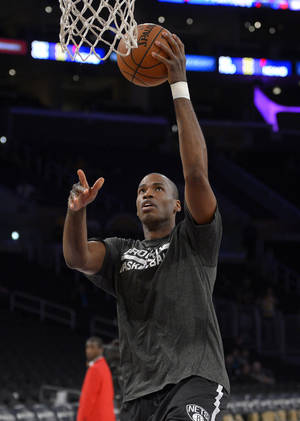 Photo - Brooklyn Nets center Jason Collins warms up prior to an NBA basketball game against the Los Angeles Lakers, Sunday, Feb. 23, 2014, in Los Angeles. Collins is set to become the NBA's first active openly gay player. He signed a 10-day contract with the Brooklyn Nets earlier Sunday and was to be in uniform for their game in Los Angeles against the Lakers. The 35-year-old center revealed at the end of last season he is gay, but he was a free agent and had remained unsigned. (AP Photo/Mark J. Terrill)