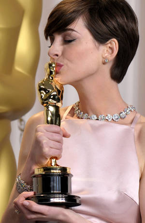 "Photo - Anne Hathaway in Prada poses with her award for best actress in a supporting role for ""Les Miserables"" during the Oscars at the Dolby Theatre on Sunday Feb. 24, 2013, in Los Angeles. (Photo by John Shearer/Invision/AP) <strong>John Shearer</strong>"