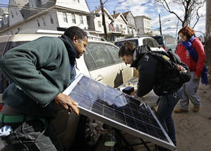 Photo - <p>Solar engineers David Gibbs, left, and Arlae Castellanos set up a solar charging station made by Castellanos's high school students on Beach 91st Street in the Rockaways, Saturday, Nov. 3, 2012, in New York. More New Yorkers awoke Saturday to power being restored for the first time since Superstorm Sandy pummeled the region, but patience wore thin among those in the region who have been without power for most of the week. (AP Photo/Kathy Willens)</p>