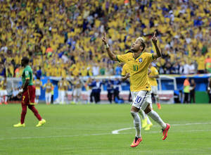 Photo - Brazil's Neymar celebrates after scoring his side's second goal during the group A World Cup soccer match between Cameroon and Brazil at the Estadio Nacional in Brasilia, Brazil, Monday, June 23, 2014. (AP Photo/Bernat Armangue)