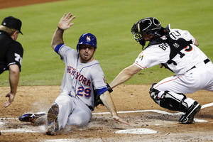 Photo -   New York Mets' Ike Davis (29) is tagged out at home plate by Miami Marlins catcher Rob Brantly (19) as home plate umpire Mike Muchinski, left, watches the play in the second inning of a baseball game in Miami, Monday, Oct. 1, 2012. (AP Photo/Alan Diaz)
