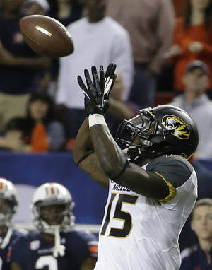 Photo - Missouri wide receiver Dorial Green-Beckham (15) makes a catch against Auburn during the first half of the Southeastern Conference NCAA football championship game, Saturday, Dec. 7, 2013, in Atlanta. Green-Beckham scored a touchdown on the play. (AP Photo/David Goldman)