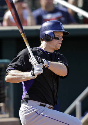 Photo - Colorado Rockies' Justin Morneau watches his bases-loaded, two-run single off Cleveland Indians starting pitcher Corey Kluber in the sixth inning of a spring exhibition baseball game Saturday, March 22, 2014, in Goodyear, Ariz. (AP Photo/Mark Duncan)