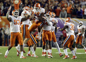 Photo - Clemson Tigers linebacker Stephone Anthony (42) celebrates with defensive end Corey Crawford (93) and linebacker Quandon Christian (34) after Anthony intercepted a pass thrown by Ohio State Buckeyes quarterback Braxton Miller during the second half of the Orange Bowl NCAA college football game, Saturday, Jan. 4, 2014, in Miami Gardens, Fla. Clemson defeated Ohio State 40-35. (AP Photo/Lynne Sladky)