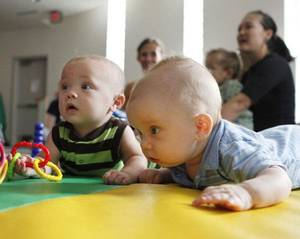Photo - Luke Saumur, left, 5 months, and Caleb Marsh, 3 months, listen to music during a Lapsit: Playtime and Story Time class at the Edmond LIbrary. PHOTO BY PAUL HELLSTERN, THE OKLAHOMAN <strong>PAUL HELLSTERN</strong>