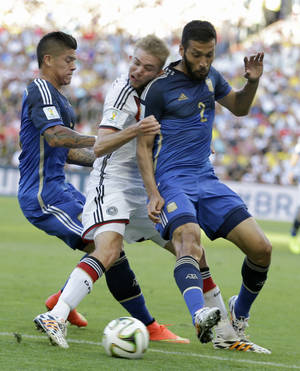 Photo - Germany's Christoph Kramer gets hit in the face by Argentina's Ezequiel Garay shoulder (2) while pinned between Garay and Marcos Rojo during the World Cup final soccer match between Germany and Argentina at the Maracana Stadium in Rio de Janeiro, Brazil, Sunday, July 13, 2014. (AP Photo/Natacha Pisarenko)