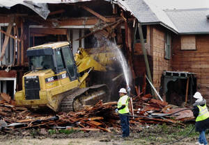 Photo - A bulldozer is used to demolish a two-story apartment building  in Dallas, Texas on Monday, January 14, 2013 where Lee Harvey Oswald briefly lived before assassinating President John F. Kennedy. The rundown building was demolished by court order after a dispute between the city and landlord Jane Bryant. (AP Photo/Nomaan Merchant)