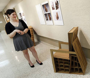 Photo - Design student Hayla Perrone looks at one of the chairs during a reception for an exhibition of cardboard chairs at UCO's Nigh University Center.  Photos by Nate Billings, The Oklahoman
