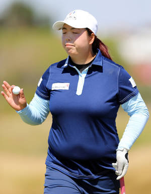 Photo - China's Shanshan Feng holds up her ball after a putt on the 9th green during the second day of the Women's British Open golf championship on the Royal Birkdale Golf Club, Southport, England, Friday July 11, 2014. (AP Photo/Scott Heppell)