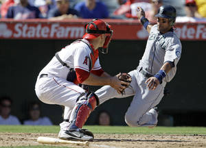 Photo -   Seattle Mariners' Franklin Gutierrez is tagged out at home by Los Angeles Angels catcher Chris Iannetta in the fifth inning of a baseball game in Anaheim, Calif., Thursday, Sept. 27, 2012. Gutierrez tried to score from first on a double by Kyle Seager (AP Photo/Reed Saxon)