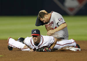 Photo - Minnesota Twiins' Trevor Plouffe (24) holds his head after he was injured on a force play at second base with Atlanta Braves second baseman Dan Uggla (26) on a ground ball in the ninth inning of a baseball game Tuesday, May 21, 2013 in  in Atlanta. (AP Photo/John Bazemore)