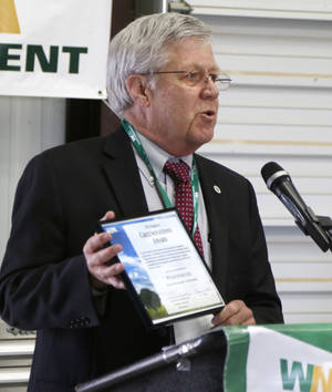Photo -  EPA Superfund Division Director Carl Edlund presents an official declaration Friday during a celebration of the deletion of the Superfund designation and the expanded gas-to-liquid facility at Waste Management's East Oak Landfill site in Oklahoma City. Photo by Paul Hellstern, The Oklahoman  <strong>PAUL HELLSTERN -  Oklahoman </strong>