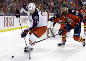 Photo - Columbus Blue Jackets center Boone Jenner (38) skates with the puck as Florida Panthers defenseman Erik Gudbranson (44) pursues in the first period of a hockey game, Saturday, April 12, 2014, in Sunrise, Fla. (AP Photo/Lynne Sladky)