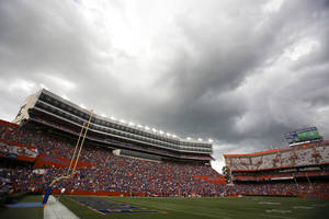 Photo - Dark clouds move over Ben Hill Griifin Stadium at Florida Field during a weather delay before the start of an NCAA college football game between Florida and Idaho in Gainesville, Fla., Saturday, Aug. 30, 2014. (AP Photo/John Raoux)
