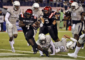 Photo - San Diego State running back Adam Muema (4) breaks through the Nevada defense to score on a 7-yard run during the second quarter of an NCAA college football game on Friday, Oct. 4, 2013, in San Diego. (AP Photo/Lenny Ignelzi)