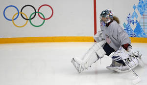 Photo - Jessie Vetter goalkeeper of the U.S. women's ice hockey team stretches during a practice session ahead of the 2014 Winter Olympics, Friday, Feb. 7, 2014, in Sochi, Russia. (AP Photo/Petr David Josek)