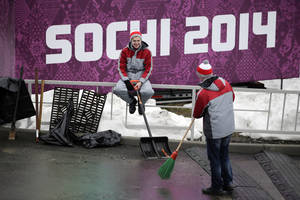 Photo - Two workers take a break at the Sanki Sliding Center, a venue for bobsleigh, skeleton and luge at the 2014 Winter Olympics, Friday, Jan. 31, 2014, in Krasnaya Polyana, Russia. (AP Photo/Jae C. Hong)