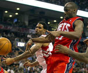 Photo -   Toronto Raptors' Gary Forbes, back, and New Jersey Nets' Johan Petro battle for the ball as it goes out of bounds during the first half of an NBA basketball game action in Toronto on Thursday, April 26, 2012. (AP Photo/The Canadian Press, Frank Gunn)