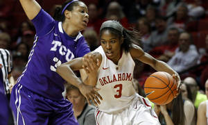 Photo - Oklahoma Sooner's Aaryn Ellenberg (3) drives around TCU Horned Frog's Veja Hamilton (3) in the second half as the University of Oklahoma Sooners (OU) defeat the Texas Christian University Horned Frogs (TCU) 63-52 in NCAA, women's college basketball at The Lloyd Noble Center on Saturday, Jan. 25, 2014 in Norman, Okla. Photo by Steve Sisney, The Oklahoman