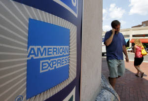 Photo - FILE - In this July 19, 2011 file photo, people walk past an American Express logo near the entrance to a bank in the Harvard Square neighborhood of Cambridge, Mass. American Express Co. on Thursday, Jan. 10, 2013 said that it will slash about 5,400 jobs, mainly in its travel business, as it seeks to cut costs and transform its operations as more of its customers shift to online portals for booking travel plans and other needs. (AP Photo/Steven Senne, File)