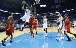 Photo - Oklahoma City Thunder forward Kevin Durant (35) shoots over Los Angeles Clippers center DeAndre Jordan (6) in the first quarter of an NBA basketball game in Oklahoma City, Thursday, Nov. 21, 2013. (AP Photo/Sue Ogrocki)