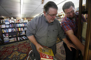 Photo - Wayne Stephens (left), owner of Archives Books in Edmond, and Logan Ray organize a case of rare books. The used book store is the second biggest seller on eBay.  <strong>Aliki Dyer - The Oklahoman</strong>