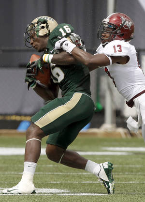 Photo -   UAB wide receiver Patrick Hearn (16) holds onto the ball as he loses his helmet on a hit from Troy cornerback T.J. Bryant (13) during the second half of an NCAA college football game in Birmingham, Ala. on Saturday, Sept. 1, 2012. Troy won 39-29. (AP Photo/Butch Dill)