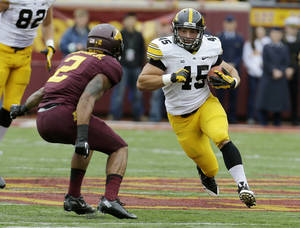 Photo - Iowa Hawkeyes fullback Mark Weisman (45) carries the ball during the first quarter of an NCAA college football game against Minnesota on Saturday, Sept. 28, 2013, in Minneapolis. (AP Photo/Ann Heisenfelt)