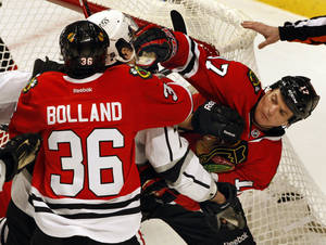 photo - Chicago Blackhawks' Sheldon Brookbank (17) and Los Angles Kings' Jordan Nolan, center, mix it up in front of the Blackhawks goal in the third period of an NHL hockey game on Sunday, Feb. 17, 2013, in Chicago. The Blackhawks won 3-2. (AP Photo/John Smierciak)