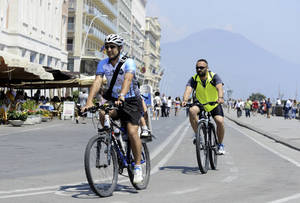 """Photo - In this Friday, June 13, 2014 photo, Luca Simeone, founder of bike-sharing start up called """"bike tour Napoli,"""" left, pedals along a cyclists' path in Naples, Italy. In the background is Mt. Vesuvius. Three years ago Naples' seafront was an urban highway, noisy and smoggy, jammed with car traffic, while smelly trash erupted from garbage bins along streets and alleys. Urban cyclers were regarded as eco-fundamentalists. Three years later, Naples has a new mayor, clean streets, a wide pedestrian beachfront and a 20-kilometer (20-mile) cycling lane overlooking a beautiful bay.  (AP Photo/Salvatore Laporta)"""