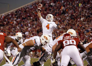 photo - Oklahoma State's J.W. Walsh (4) grabs a high hike during the Bedlam college football game between the University of Oklahoma Sooners (OU) and the Oklahoma State University Cowboys (OSU) at Gaylord Family-Oklahoma Memorial Stadium in Norman, Okla., Saturday, Nov. 24, 2012. OU won 51-48 in overtime. Photo by Sarah Phipps, The Oklahoman