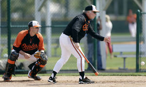 Photo - Baltimore Orioles manager Buck Showalter tosses the ball in front of catcher Matt Wieters, left, during a drill in a baseball spring training workout Saturday, Feb. 16, 2013, in Sarasota, Fla. (AP Photo/Charlie Neibergall)