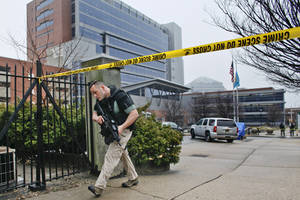 Photo - Law enforcement officials makes his way around the perimeter outside the New Castle County Courthouse in Wilmington, Del. on Monday Feb. 11, 2013, after three people died Monday morning in a shooting at a courthouse, including the shooter, authorities said.  (AP Photo/ Joseph Kaczmarek)