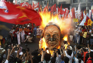 photo -   Protesters burn an effigy of Philippine President Benigno Aquino III during a rally near the Presidential Palace in Manila to celebrate international Labor Day known as May Day Tuesday May 1, 2012 in the Philippines. Thousands of workers marched under a brutal sun in Manila to demand a wage increase amid an onslaught of oil price increases, but the Philippine President rejected a $3 daily pay hike which the workers have been demanding since 1999 and warned may worsen inflation, spark layoffs and turn away foreign investors. (AP Photo/Bullit Marquez)