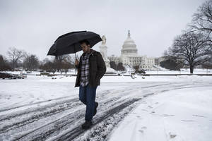 Photo - A man walks through the slush and shields himself from freezing rain on Capitol Hill in Washington, Thursday, Feb. 13, 2014, as winter weather shuts down Washington. After pummeling wide swaths of the South, a winter storm dumped nearly a foot of snow in Washington as it marched Northeast and threatened more power outages, traffic headaches and widespread closures for millions of residents. (AP Photo/J. Scott Applewhite)